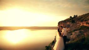 Γαμήλιο ζεύγος στην παραλία στο ηλιοβασίλεμα απόθεμα βίντεο