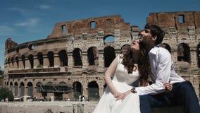 Γαμήλιο ζεύγος στη Ρώμη από Coliseum τη συνεδρίαση δίπλα-δίπλα και αγκαλιάζοντας το ένα άλλη Μήνας του μέλιτος στην Ιταλία, Ευρώπ απόθεμα βίντεο