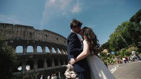 Γαμήλιο ζεύγος στο φίλημα της Ρώμης κοντά στο Coliseum Ξυπόλυτη νύφη που κρατά τα παπούτσια της διαθέσιμα Μήνας του μέλιτος στην  φιλμ μικρού μήκους