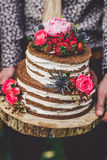 Γαμήλιο κέικ λαβής νεόνυμφων με τα λουλούδια Στοκ φωτογραφία με δικαίωμα ελεύθερης χρήσης