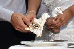 Γαμήλιο κέικ φετών περικοπών νυφών και νεόνυμφων Στοκ Φωτογραφίες