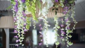 Γαμήλιο ντεκόρ των λουλουδιών σε έναν πολυέλαιο σε ένα εστιατόριο απόθεμα βίντεο