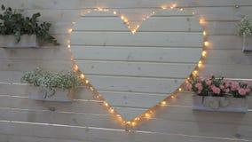 Γαμήλιο ντεκόρ των λουλουδιών σε ένα δοχείο και μια μεγάλη άσπρη ξύλινη καρδιά φιλμ μικρού μήκους