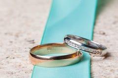 Γαμήλιο δύο δαχτυλίδι του άσπρου και κίτρινου χρυσού στο πράσινο λουρί Στοκ φωτογραφία με δικαίωμα ελεύθερης χρήσης