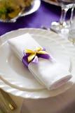 Γαμήλιο doily λευκό με το πορφυρό, κίτρινο bowknot, διακόσμηση στο πιάτο στον πίνακα Στοκ Εικόνα