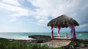 Γαμήλιο gazebo στην ωκεάνια ακτή σκοπέλων φιλμ μικρού μήκους