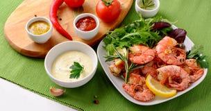 Γαρίδες γαρίδων που μαγειρεύονται με το σκόρδο και το δεντρολίβανο, που εξυπηρετούνται στο άσπρο πιάτο Στοκ Φωτογραφίες