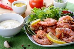 Γαρίδες γαρίδων που μαγειρεύονται με το σκόρδο και το δεντρολίβανο, που εξυπηρετούνται στο άσπρο πιάτο Στοκ Εικόνες