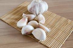 Γαρίφαλα σκόρδου στο χαλί makisu στην ξύλινη σύσταση στοκ φωτογραφία