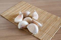 Γαρίφαλα σκόρδου στο χαλί makisu στην ξύλινη σύσταση στοκ φωτογραφίες με δικαίωμα ελεύθερης χρήσης