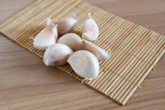 Γαρίφαλα σκόρδου στο χαλί makisu στην ξύλινη σύσταση στοκ φωτογραφία με δικαίωμα ελεύθερης χρήσης