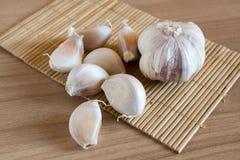 Γαρίφαλα σκόρδου στο χαλί makisu στην ξύλινη σύσταση στοκ εικόνα με δικαίωμα ελεύθερης χρήσης