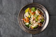 Γαρίδες και σαλάτα αβοκάντο στο εκλεκτής ποιότητας μεταλλικό πιάτο στο γκρίζο τραπεζομάντιλο Στοκ Εικόνες