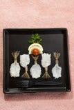 Γαρίδες πεταλούδων με το λεμόνι και την ντομάτα στο μαύρο πιάτο με το ρόδινο υπόβαθρο Στοκ εικόνες με δικαίωμα ελεύθερης χρήσης