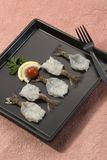Γαρίδες πεταλούδων με το λεμόνι και την ντομάτα στο μαύρο πιάτο με το ρόδινο υπόβαθρο Στοκ Φωτογραφίες