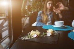 Γαρίδες τιγρών στα κινεζικά νουντλς με τη σάλτσα στο μαύρο πιάτο ασιατικά τρόφιμα έννοιας Οι άνθρωποι στο υπόβαθρο στο εστιατόριο Στοκ Εικόνες