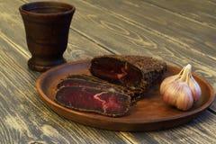 γαστρονομικός Εύγευστος ορεκτικός jerky με τα καρυκεύματα και το σκόρδο στο κεραμικό πιάτο και κεραμικό φλυτζάνι στο σκοτεινό τρα στοκ εικόνες