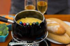 Γαστρονομικό ελβετικό fondue γεύμα με τα ανάμεικτα τυριά και ένα θερμαμένο δοχείο fondue τυριών με τα ζωηρόχρωμα δίκρανα που βυθί Στοκ Εικόνα