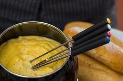 Γαστρονομικό ελβετικό fondue γεύμα με τα ανάμεικτα τυριά και ένα θερμαμένο δοχείο fondue τυριών με τα ζωηρόχρωμα δίκρανα που βυθί Στοκ φωτογραφία με δικαίωμα ελεύθερης χρήσης