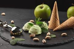 Γαστρονομικό παγωτό φυστικιών που εξυπηρετείται σε μια πλάκα πετρών πέρα από ένα μαύρο υπόβαθρο στοκ φωτογραφία