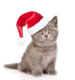 Γατάκι με το κόκκινο καπέλο Χριστουγέννων που ανατρέχει Απομονωμένος στο λευκό Στοκ Φωτογραφία