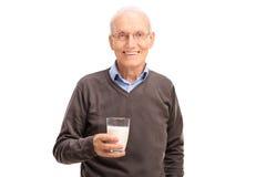 Γαλήνιος ανώτερος κύριος που κρατά ένα ποτήρι του γάλακτος στοκ φωτογραφία