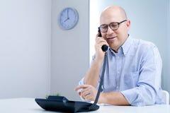 Γαλήνιος εργαζόμενος γραφείων στο τηλέφωνο Στοκ Εικόνες