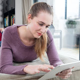 Γαλήνιος πανέμορφος θηλυκός έφηβος σχετικά με την ταμπλέτα της στην αναζήτηση on-line στοκ εικόνα με δικαίωμα ελεύθερης χρήσης
