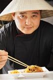 Γαλήνιος τύπος στο κωνικό ασιατικό καπέλο που έχει το γεύμα Στοκ Φωτογραφία