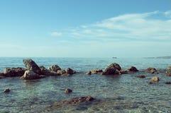 Γαλήνιο seascape με τους βράχους στο πρώτο πλάνο και τη βάρκα στον ορίζοντα Στοκ φωτογραφία με δικαίωμα ελεύθερης χρήσης