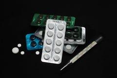 Γαλαζοπράσινα άσπρα χάπια θερμομέτρων στο μαύρο υπόβαθρο Στοκ φωτογραφία με δικαίωμα ελεύθερης χρήσης