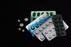 Γαλαζοπράσινα άσπρα χάπια στο μαύρο υπόβαθρο Στοκ Φωτογραφίες