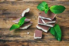 Γαλακτώδης πορώδης άσπρη και σκοτεινή σοκολάτα με τα φύλλα μεντών Στοκ Φωτογραφία