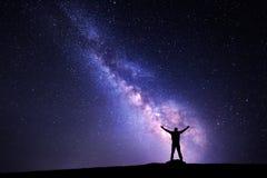 Γαλακτώδης τρόπος Νυχτερινός ουρανός και σκιαγραφία ενός μόνιμου ατόμου Στοκ Φωτογραφία