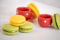 Γαλλικά ζωηρόχρωμα macarons με teapot και ένα φλυτζάνι Στοκ Εικόνα