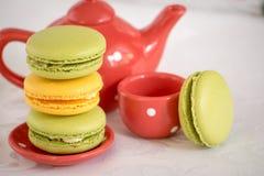Γαλλικά ζωηρόχρωμα macarons με teapot και ένα φλυτζάνι Στοκ εικόνα με δικαίωμα ελεύθερης χρήσης