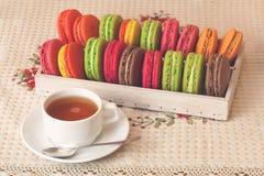 Γαλλικά ζωηρόχρωμα macarons στο κιβώτιο, φλυτζάνι του τσαγιού, τρύγος που τονίζεται Στοκ Εικόνα