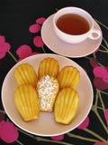 Γαλλικά madeleines και τσάι στο ρόδινο τρύγο dishware στο μαύρο και ροδανιλίνης τραπεζομάντιλο κεράσι-σχεδίων Στοκ εικόνα με δικαίωμα ελεύθερης χρήσης
