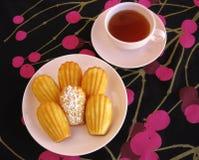 Γαλλικά madeleines και τσάι στο ρόδινο τρύγο dishware στο μαύρο και ροδανιλίνης τραπεζομάντιλο κεράσι-σχεδίων Στοκ φωτογραφία με δικαίωμα ελεύθερης χρήσης