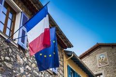 Γαλλικές και ευρωπαϊκές σημαίες που κρεμιούνται σε μια αρχαία αίθουσα πόλεων Στοκ Εικόνες