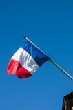 Γαλλική σημαία ενάντια στον μπλε νεφελώδη ουρανό Στοκ Εικόνες