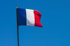 Γαλλική σημαία ενάντια στον μπλε νεφελώδη ουρανό Στοκ Φωτογραφία