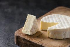 Γαλλικό μαλακό τυρί από την περιοχή της Νορμανδίας με μια φέτα σε έναν ξύλινο πίνακα Στοκ φωτογραφία με δικαίωμα ελεύθερης χρήσης