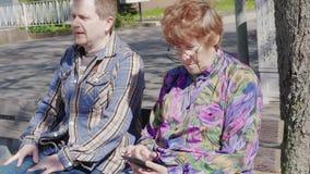 Γείτονες στον πάγκο με τα κινητά τηλέφωνα υπαίθρια, συγκινήσεις απόθεμα βίντεο