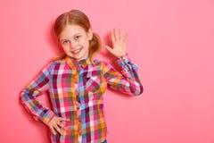 Γειά σου! Η όμορφη στάση μικρών κοριτσιών με το αυξημένο χέρι, χαμογελώντας και σας καλωσορίζει στο ρόδινο υπόβαθρο Στοκ Εικόνα