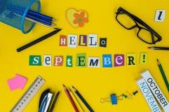 Γειά σου κείμενο Σεπτεμβρίου στο ανοικτό κίτρινο υπόβαθρο με το σχολείο suplies Πίσω στην έννοια σχολικού χρόνου Στοκ Φωτογραφίες