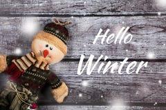 Γειά σου χειμερινή ευχετήρια κάρτα με το μαλακό παιχνίδι χιονανθρώπων στο γκρίζο ξύλινο υπόβαθρο Στοκ Φωτογραφία
