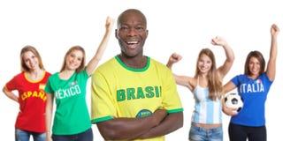 Γελώντας άτομο από τη Βραζιλία με τέσσερις θηλυκούς αθλητικούς ανεμιστήρες Στοκ εικόνες με δικαίωμα ελεύθερης χρήσης