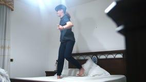 Γελώντας άτομο που πηδά και που χορεύει σε ένα άσπρο κρεβάτι φιλμ μικρού μήκους