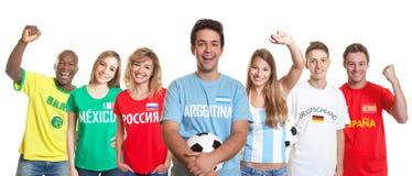 Γελώντας αργεντινός υποστηρικτής ποδοσφαίρου με τη σφαίρα και ανεμιστήρες από το ot στοκ εικόνα
